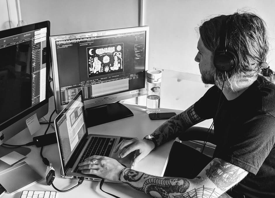Image of Sam a long haired tattooed designer in front of 3 screens